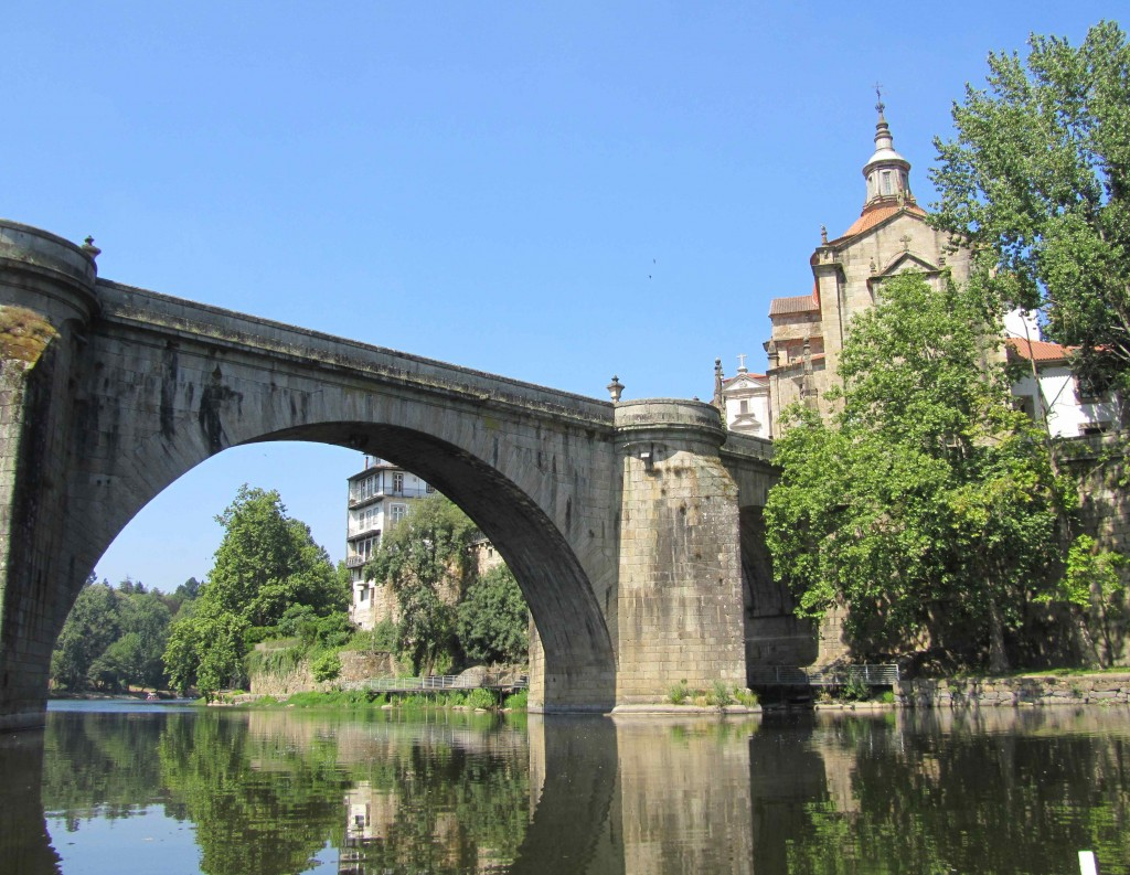 View of the Medieval bridge and monastery from a row boat in the river, Amarante